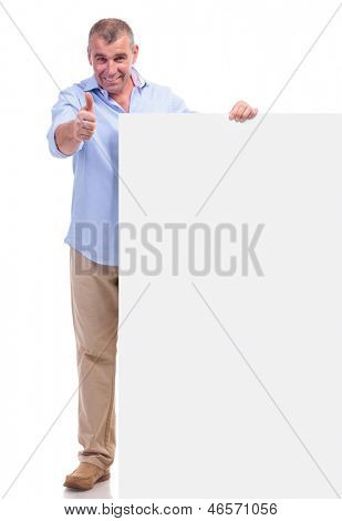casual senior man holding a blank pannel and showing the thumbs up gesture to the camera with a smile on his face. isolated on white background