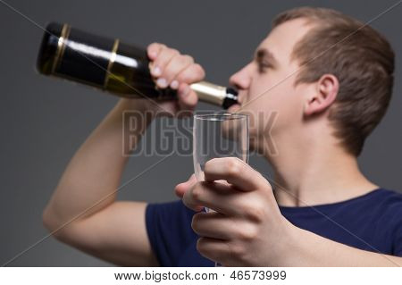 Young Drunk Man With Bottle Of Alcohol And Glass