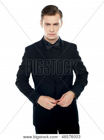 Serious Young Man Tucking Coat Button
