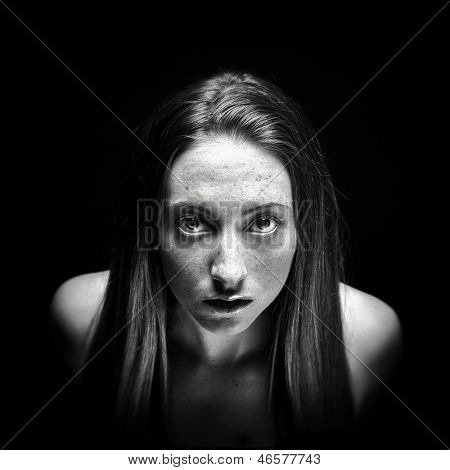 Stark, low key portrait of a young woman emerging from the darkness