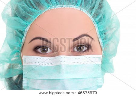 Close Up Portrait Of Female Doctor In Blue Mask And Cap Over White