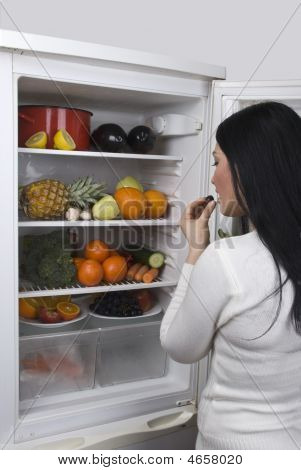 Woman And Full Fridge With Fresh Fruits And Vegetables