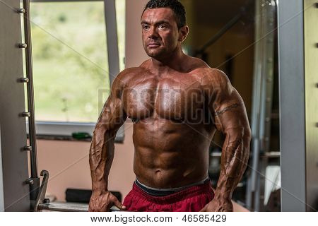 Male Bodybuilder Doing Heavy Weight Exercise For Trap