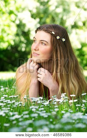 Portrait Of A Beautiful Young Woman Lying On Green Grass Outdoors
