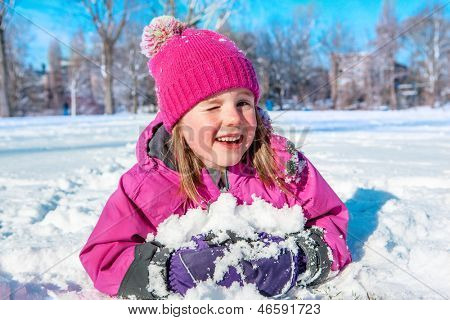 Child in winter clothes lying on the snow and winking