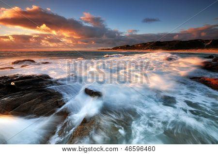 Waves crashing on a rock at sunset