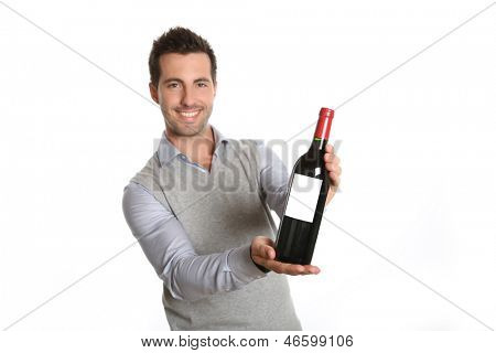 Happy winegrower showing wine bottle to camera