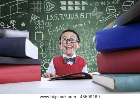 Asian Boy Laughing In Class With Stack Of Books