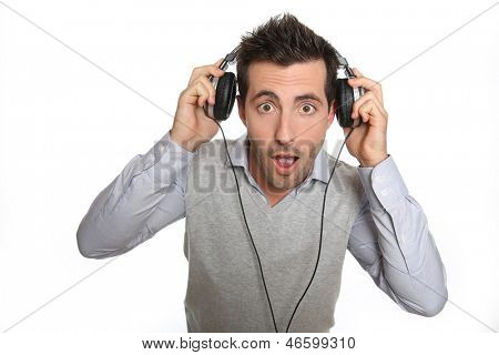 Portrait of astonished guy taking headphones off