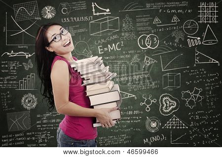 Attractive female student bring stack of books in class