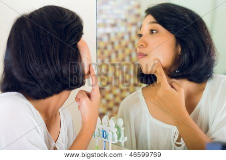 Asian woman discovering a pimple in face
