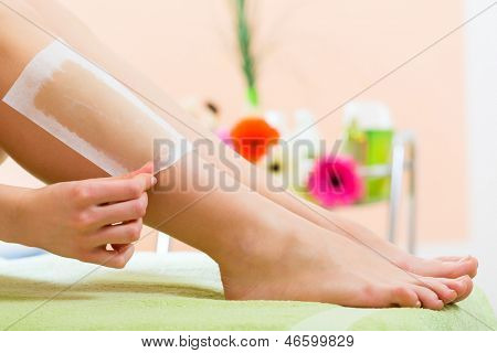 Young woman in Spa getting legs waxed for hair removal