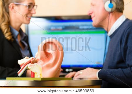 Older man or pensioner with a hearing problem make a hearing test and may need a hearing aid, in the foreground is a model of a human ear