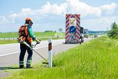 stock photo of grass-cutter  - Road landscapers cutting grass around mileposts along the road using string lawn trimmers - JPG