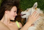 image of tickling  - beautiful young happy laugh girl playing with her dog outdoor - JPG