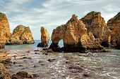 stock photo of grotto  - Rocky cliffs on the coast of the Atlantic ocean in Lagos Algarve Portugal - JPG