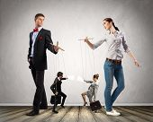 foto of male-domination  - Image of man and woman with marionette puppets - JPG