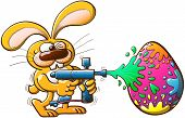 picture of paintball  - Nice bunny having fun while winking and painting a huge Easter egg with a modern paintball gun - JPG