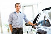 stock photo of designated driver  - young man standing near a car in a showroom - JPG