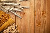 image of whole-wheat  - Pasta with wheat ear on wooden background - JPG