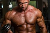 stock photo of muscle builder  - bodybuilder doing heavy weight exercise for biceps with dumbbell - JPG