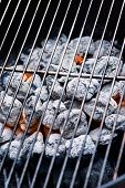 stock photo of briquette  - Glowing charcoals briquettes on the grill lattice - JPG