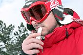 Skier applying lip balm