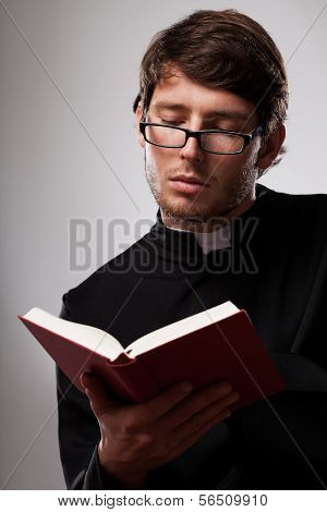 Young Clergyman Studying A Bible