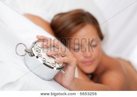 Beautiful Sleeping Woman Holding Alarm Clock