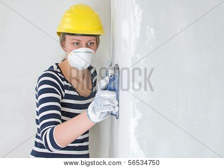 Female Plasterer In Hard Hat Polishing The Wall. Place For Your Text.