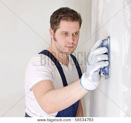 Male Plasterer In Uniform Polishing The Wall.