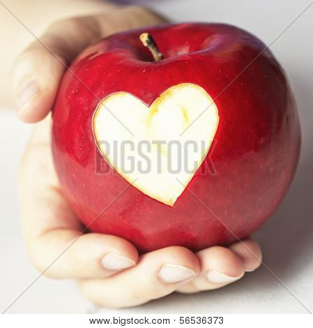 Hand holding red apple with heart