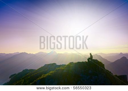 lonely sad girl sitting on mountain summit looking over alps