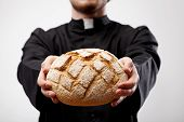 stock photo of eucharist  - Priest holding loaf of bread as an Eucharist - JPG