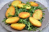 stock photo of rocket salad  - Fried potatoes with green rocket salad on a plate - JPG