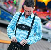 stock photo of lederhosen  - Funny bavarian man checking his lederhosen trousers - JPG