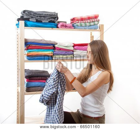 Young caucasian woman standing near the wardrobe with shirt