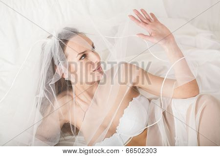 Woman In Bridal Lingerie Covering Her Face Using Veil