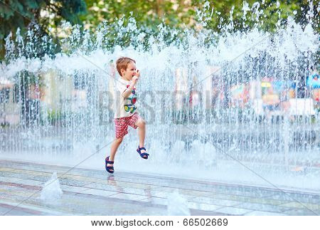 Excited Boy Running Between Water Flow In City Park