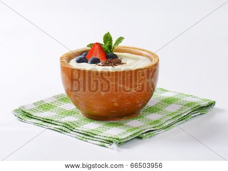 warm semolina pudding with fresh berries, served in the ceramic bowl