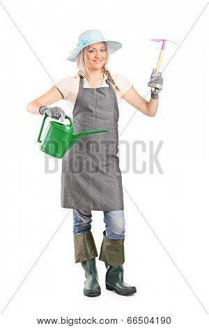 Full length portrait of a female gardener holding mattock and watering can isolated on white background