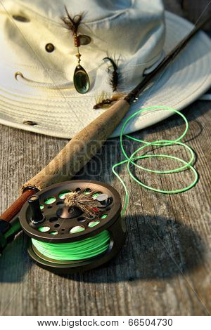 Close-up of fly-fishing reel and rod with canvas hat