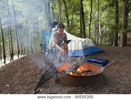 teenager at campsite with tent and camp fire