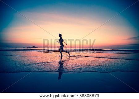 Blured silhouette of a woman jogger on the beach at sunset, surreal colours.
