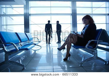 Businesswoman reading at the airport on background of colleagues talking by the window
