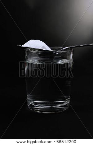 Spoon of baking soda over glass of water on black background
