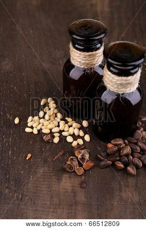 Cedar pine nuts and bottles of essential oil on wooden background