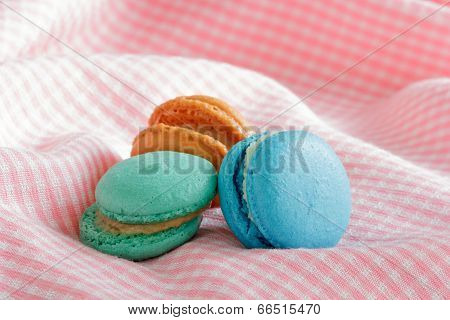 Group Of Colorful Macaroons On Pink Cloth.