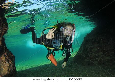 Young Woman Scuba diving into underwater cave