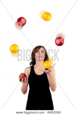 Beautiful Woman Juggling Apples And Oranges On A White Backgroun